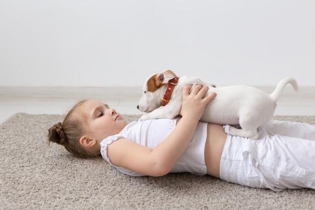 Zwierzęta domowe i koncepcja zwierząt - dziewczynka bawi się ze szczeniakiem jack russell terrier