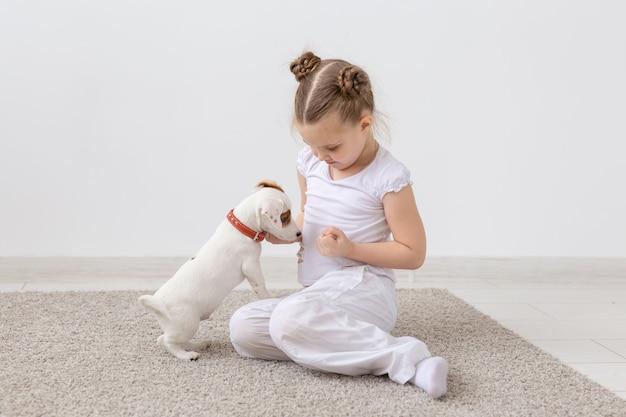 Zwierzęta i koncepcja zwierząt - dziewczynka bawi się ze szczeniakiem jack russell terrier