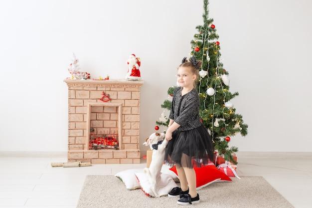 Zwierzęta, święta i koncepcja bożego narodzenia - dziewczyna dziecko bawi się szczeniaka jack russell terrier w pobliżu choinki.