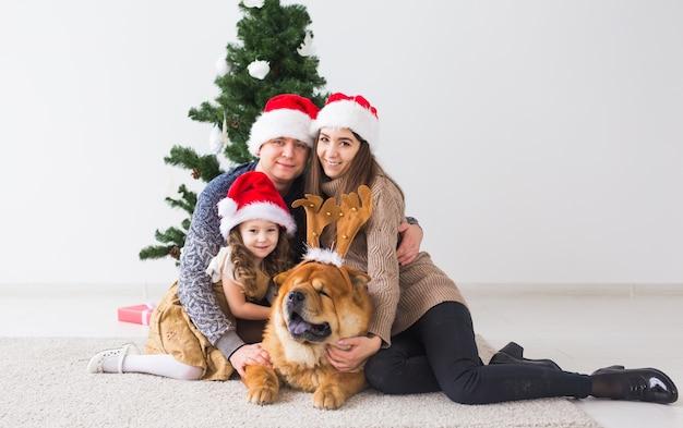 Zwierzęta, wakacje i koncepcja świąteczna - rodzina z psem siedzi na podłodze w pobliżu choinki.