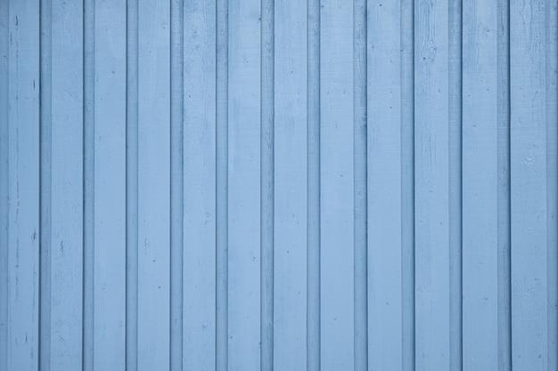 Zwietrzała drewniana pomalowana na niebiesko ściana w skandynawii