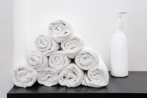 Zwinięte białe ręczniki z butelką kosmetyczną. butelka mydła i białe ręczniki zwinięte na stole do spa.