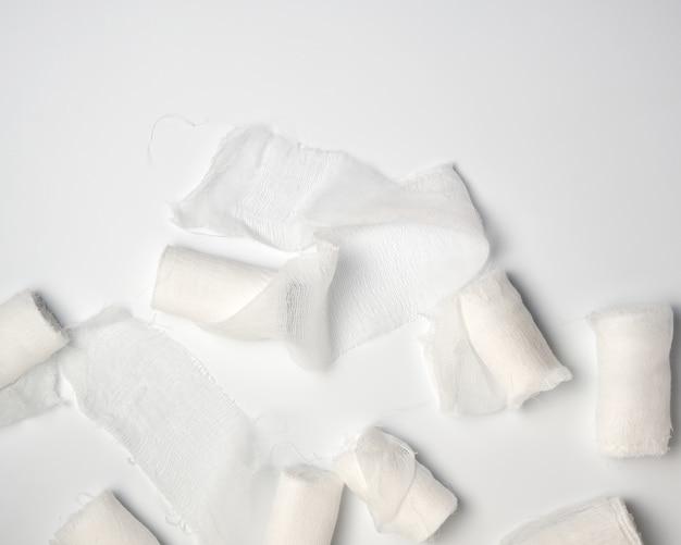 Zwinięte białe sterylne medyczne bandaże na białym