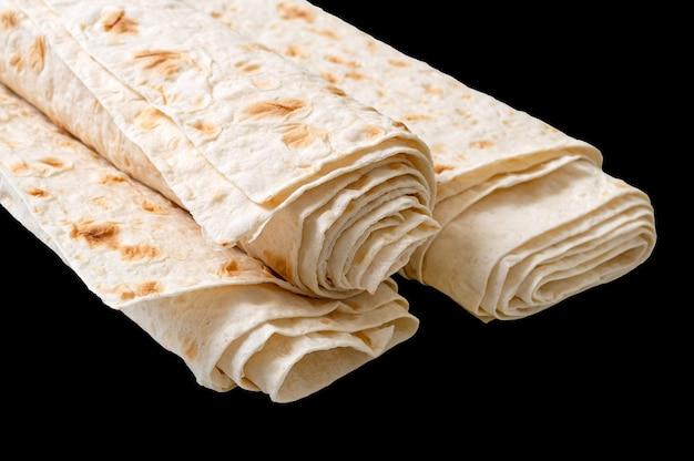 Zwinięte cienki chleb pita na białym na czarnym tle.