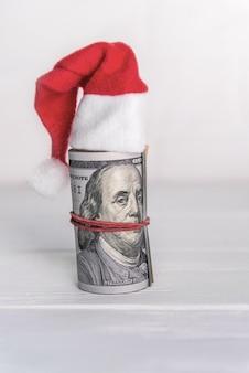 Zwinięte dolary w czapce mikołaja. na drewnianym biurku