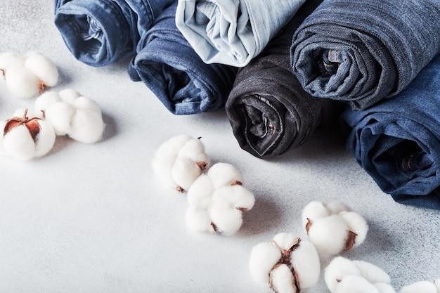 Zwinięte dżinsy i bawełniane kwiaty na jasnym stole