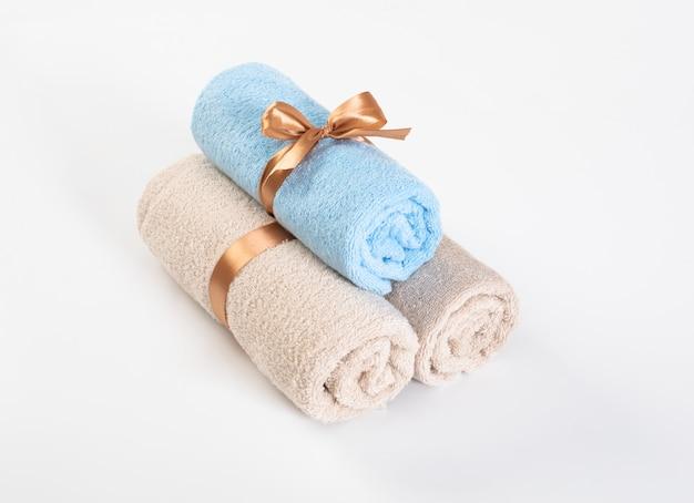 Zwinięte niebieskie i różowe ręczniki frotte na białym tle