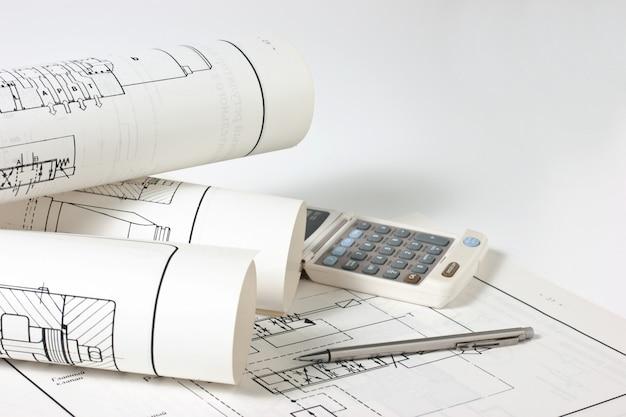 Zwinięte rysunki techniczne i kalkulator