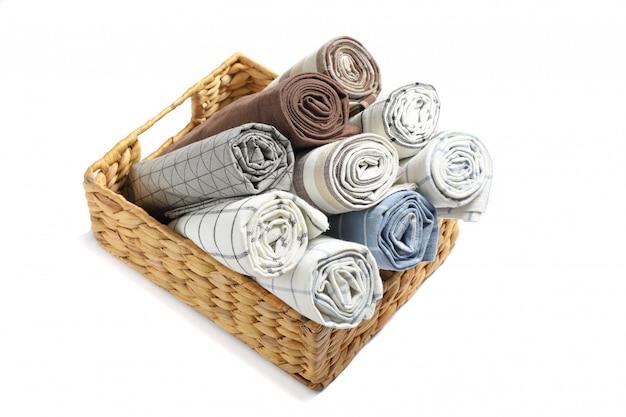 Zwinięte tkaniny serwetki w koszu na białym tle