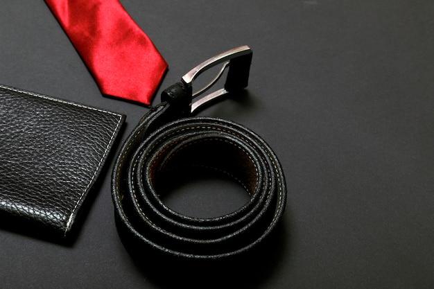 Zwinięty czerwony krawat męski i skórzany pas