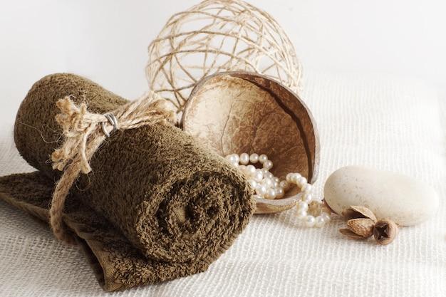 Zwinięty ręcznik i perły w kokosie na lekkiej tkanej serwetce, przygotowanie do zabiegu spa.