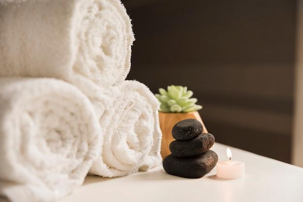 Zwinięty ręcznik z kamieniem spa i podświetlaną świecą na stole
