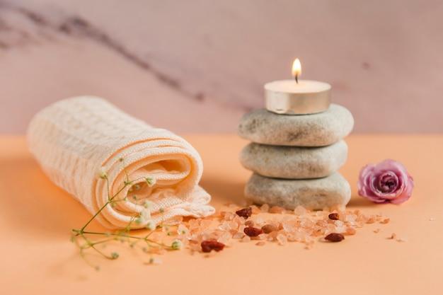 Zwinięty ręcznik; zapalona świeca nad kamieniami spa; róża i sole himalajskie na kolorowym tle brzoskwini