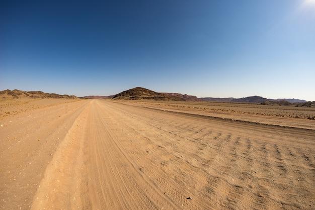 Żwir 4x4 droga krzyżuje kolorową pustynię przy twyfelfontein, w majestatycznym damaraland brandberg, sceniczny podróży miejsce przeznaczenia w namibia, afryka.