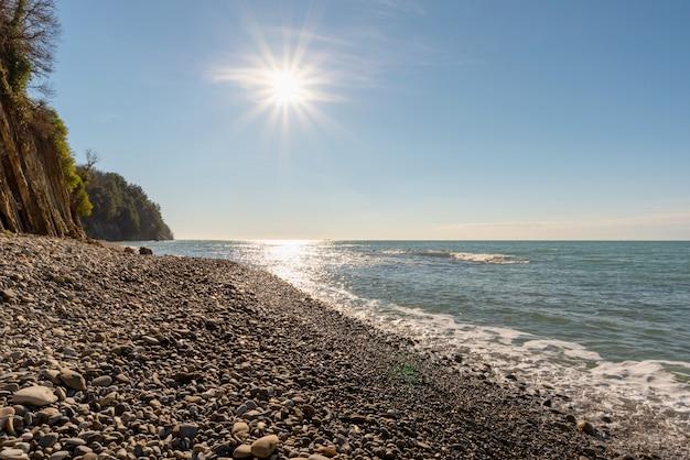Żwirowa plaża, jasne wieczorne słońce w tuapse, rosja
