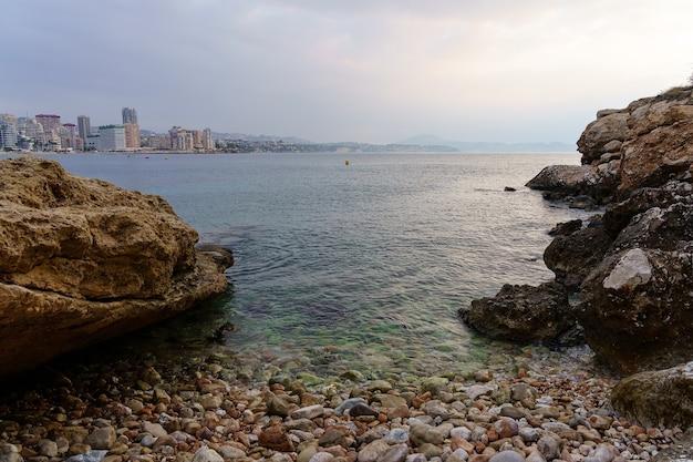 Żwirowa plaża obok skał i widok na letnie miasto w tle.