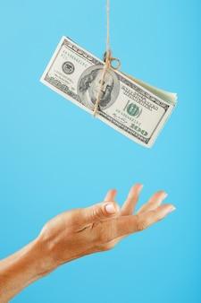 Zwitek dolarów na sznurku powyżej ludzkiej dłoni na niebiesko.