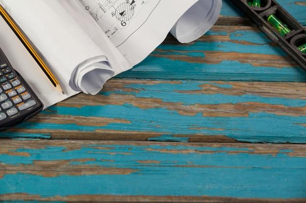 Zwoje papieru, ołówek, kalkulator i poziomica