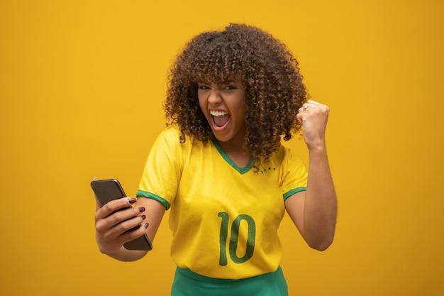 Zwolennik brazylijskiej drużyny futbolowej świętuje bramkę, oglądając smartfon