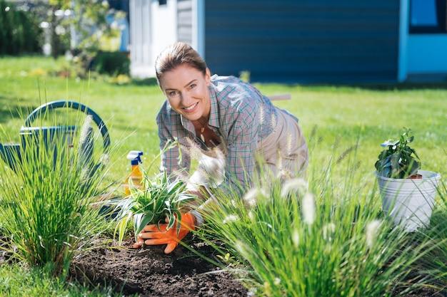 Zwolennik środowiska. piękna uśmiechnięta gospodyni domowa jest wielką zwolenniczką czystego środowiska, spędzając poranek przy kwietniku
