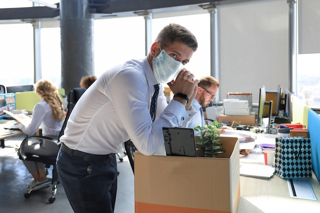 Zwolnienie pracownika w prewencyjnej masce medycznej w epidemii koronawirusa. smutny zwolniony pracownik zabiera ze sobą przybory biurowe z biura.