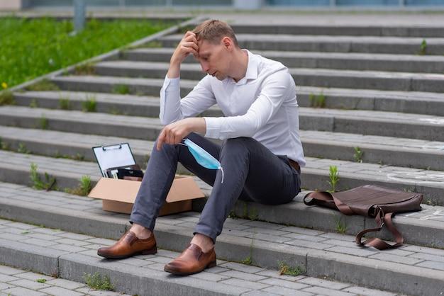 Zwolnienie pracownika z powodu epidemii koronawirusa. na schodach siedzi mężczyzna. obok niego jest jego artykuły papiernicze.