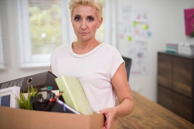 Zwolniona kobieta niosąca pudełko z jakąś zawartością