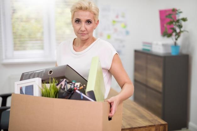 Zwolniona kobieta z pudełkiem pełnym rzeczy osobistych