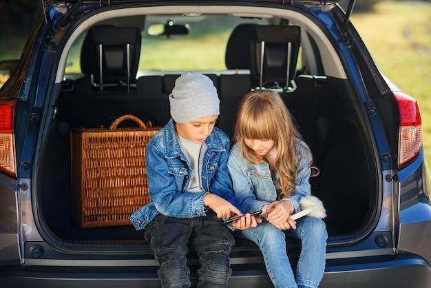 Zwolnione tempo blond 12-letniej dziewczynki i przystojnego 10-letniego chłopca w dżinsach, które siedzą w bagażniku i patrzą na swojego smartfona