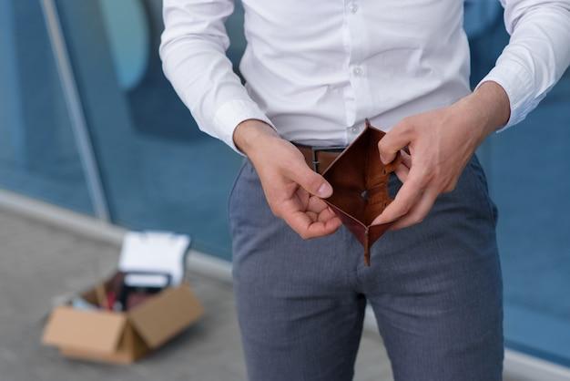 Zwolniony pracownik z powodu kryzysu otwiera pokazując swój pusty portfel.
