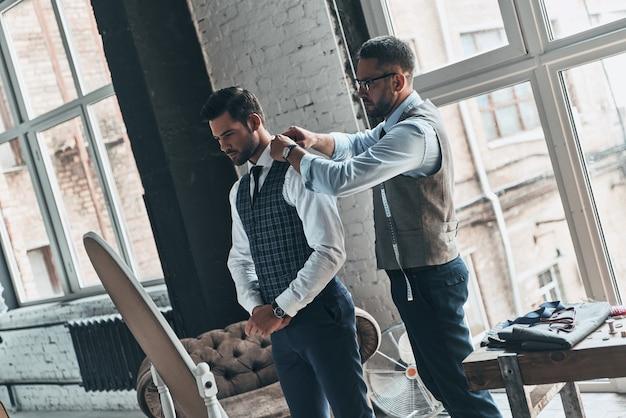Zwracając uwagę na każdy szczegół. młody modny projektant pomagający swojemu klientowi się ubrać