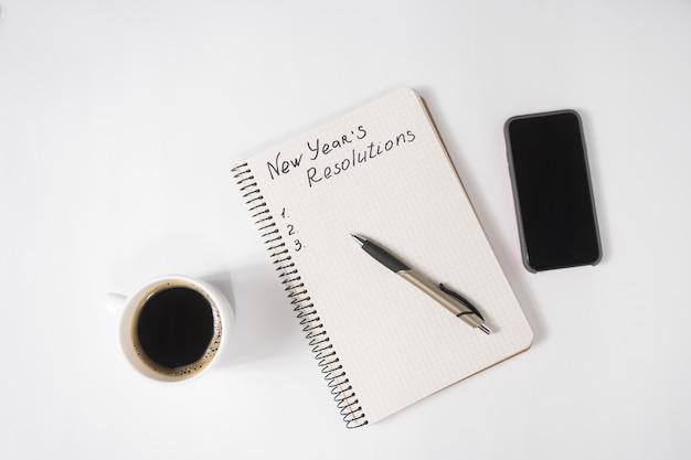 Zwrot noworoczne postanowienia w notatniku i piórze, filiżance kawy i smartfonie na stole