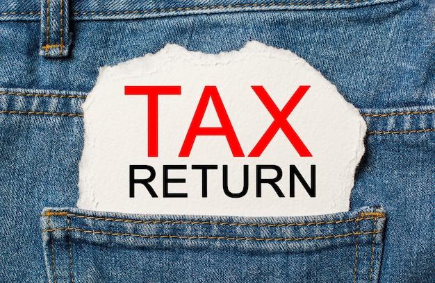 Zwrot podatku na rozdartym tle papieru na koncepcji dżinsów biznesowych i finansowych