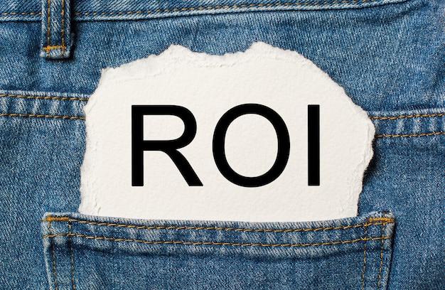 Zwrot z inwestycji na rozdartym tle papieru na koncepcji dżinsów i finansów