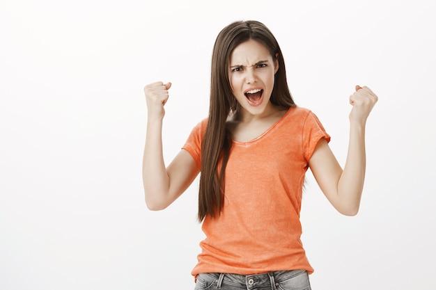Zwycięska i wzmocniona pompa pięścią młodej dziewczyny. motywowanie się, osiągnięcie celu, świętowanie zwycięstwa