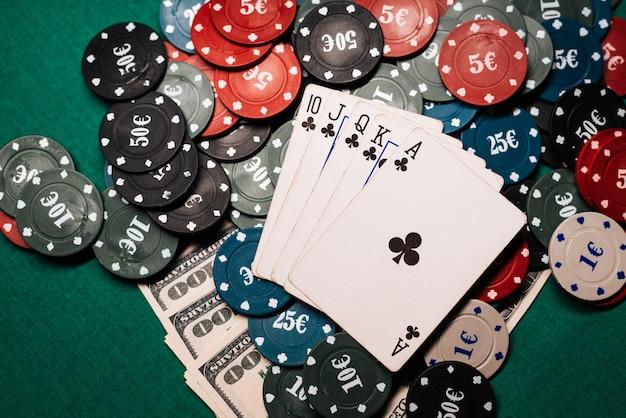 Zwycięska kombinacja kart w pokerze kasynowym. poker królewski, kilka żetonów i dolarów pieniężnych