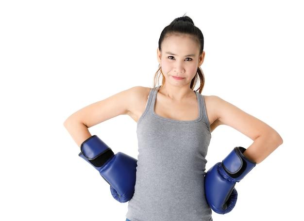 Zwycięska młoda azjatycka zawodniczka w niebieskich rękawicach bokserskich podnosząca ręce i uśmiechająca się radośnie podczas świętowania triumfu na białym tle
