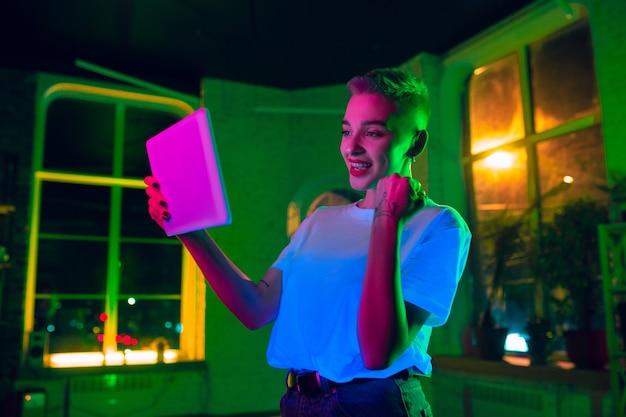 Zwycięski. kinowy portret stylowej kobiety w oświetlonym neonem wnętrzu. stonowane jak efekty kinowe, jasne neonowane kolory. model kaukaski za pomocą tabletu w kolorowych światłach w pomieszczeniu. kultura młodzieżowa.