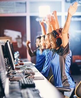 Zwycięski. młody wielorasowy zespół szczęśliwych profesjonalnych graczy cybersportowych świętujących sukces, podnoszący ręce do góry podczas udziału w turnieju e-sportowym, grający w gry wideo online