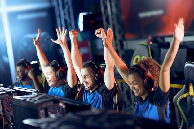 Zwycięski. zespół szczęśliwych profesjonalnych graczy cybersportowych świętujących sukces podczas udziału w turnieju e-sportowym, grający w gry wideo online