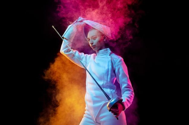 Zwycięskie myśli. teen dziewczyna w stroju szermierki z mieczem w ręku na białym tle neon oświetlony dym. ćwiczenie treningu w ruchu, działaniu. copyspace. sport, młodość, zdrowy tryb życia.