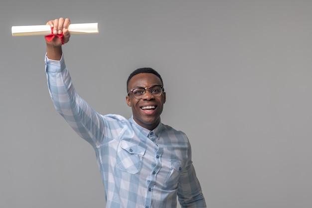Zwycięstwo, emocje. radosny energiczny ciemnoskóry mężczyzna w okularach podnoszący rękę z pakietem papieru na jasnym tle