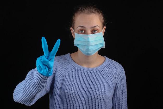 Zwycięstwo nad covid-19. kobieta w medycznej masce na twarz i rękawiczkach pokazuje symbol zwycięstwa na czarnej ścianie.
