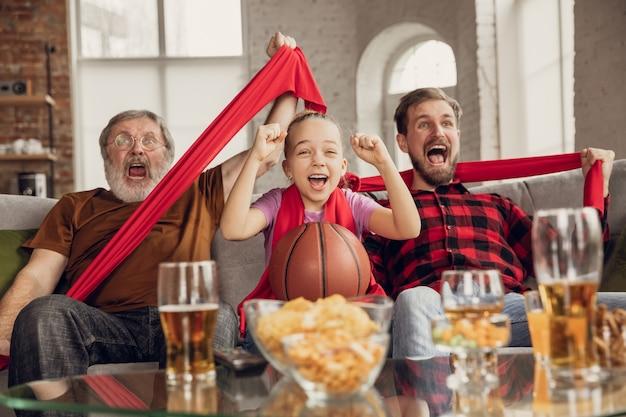 Zwycięstwo. podekscytowana, szczęśliwa rodzina ogląda mecz koszykówki, mistrzostwa na kanapie w domu. kibice emocjonalnie dopingowali ulubioną drużynę narodową. córka, tata i dziadek. sport, telewizja, dobra zabawa.