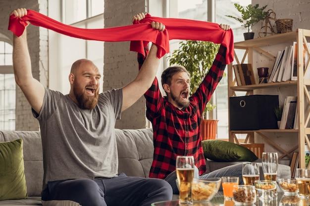 Zwycięstwo. podekscytowani, szczęśliwi przyjaciele oglądają koszykówkę, piłkę nożną, piłkę nożną, mecz tenisa, mistrzostwa na kanapie w domu. kibice emocjonalnie dopingowali ulubioną drużynę narodową. sport, telewizja, dobra zabawa.