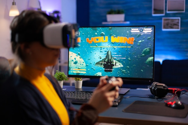 Zwycięzca grający w kosmiczne strzelanki, noszący zestaw wirtualnej rzeczywistości podczas mistrzostw. wirtualne cyberprzesyłanie strumieniowe online podczas turnieju gry za pomocą technologii bezprzewodowej sieci
