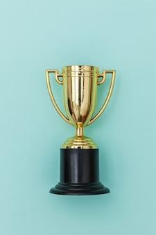 Zwycięzca lub mistrz złoty puchar trofeum na białym tle na niebieskim pastelowym kolorowym tle