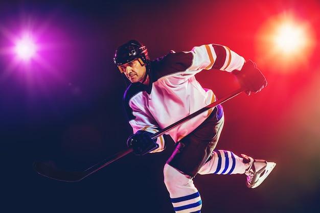 Zwycięzca. męski hokeista z kijem na boisku i ciemną neonową ścianą. sportowiec noszący sprzęt, ćwiczący kask. pojęcie sportu, zdrowego stylu życia, ruchu, odnowy biologicznej, działania.