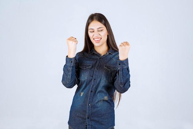 Zwycięzca młoda kobieta pokazująca pięści i czująca siłę