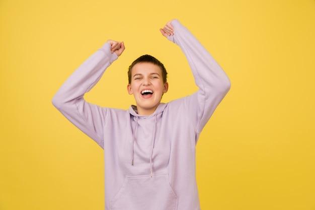 Zwycięzca. portret dziewczyny kaukaski na białym tle na żółtym tle studio z copyspace dla reklamy. piękna modelka w bluzie z kapturem. pojęcie ludzkich emocji, wyraz twarzy, sprzedaż, reklama, moda.